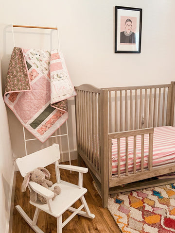 pink and green floral quilt in baby nursery