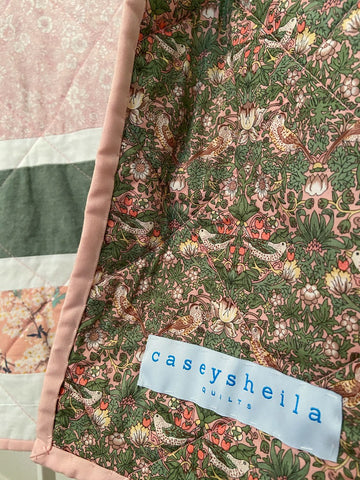pink and green liberty of london backing on baby girl quilt