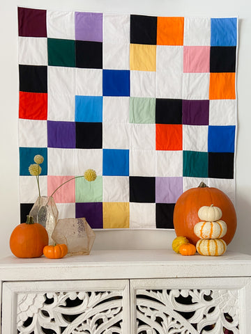 colorful wall quilt styled with pumpkins
