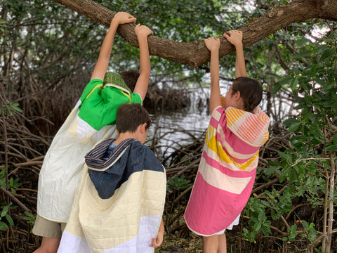 kids hanging on a tree branch with quilts acting like wild things