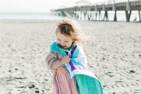 little girl wearing a happy quilt on the beach