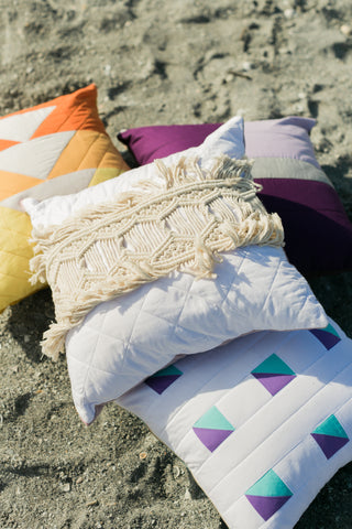 four quilted pillows in a pile on the beach