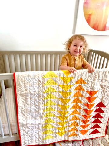 quilt hanging on crib in nursery