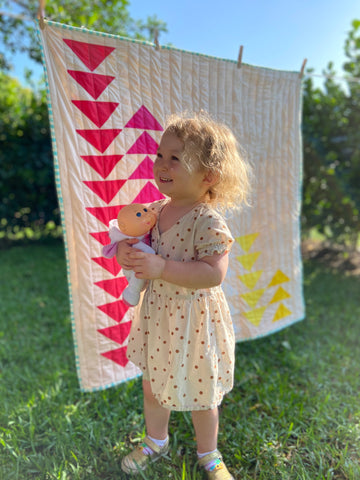 toddler girl standing in front of quilt outside