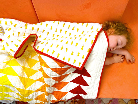 quilt laying on sleeping toddler