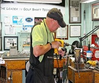 David Bass working on a golf club.