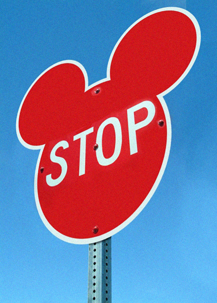 A stop sign shaped like the Mickey Mouse logo