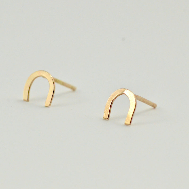 A closeup of our gold horseshoe studs
