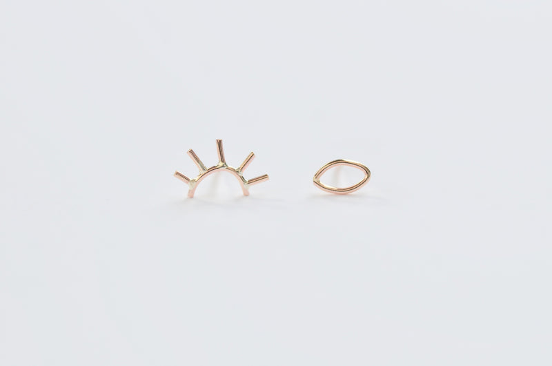 Our pair of gold open eye studs, one eye is open and the other is winking