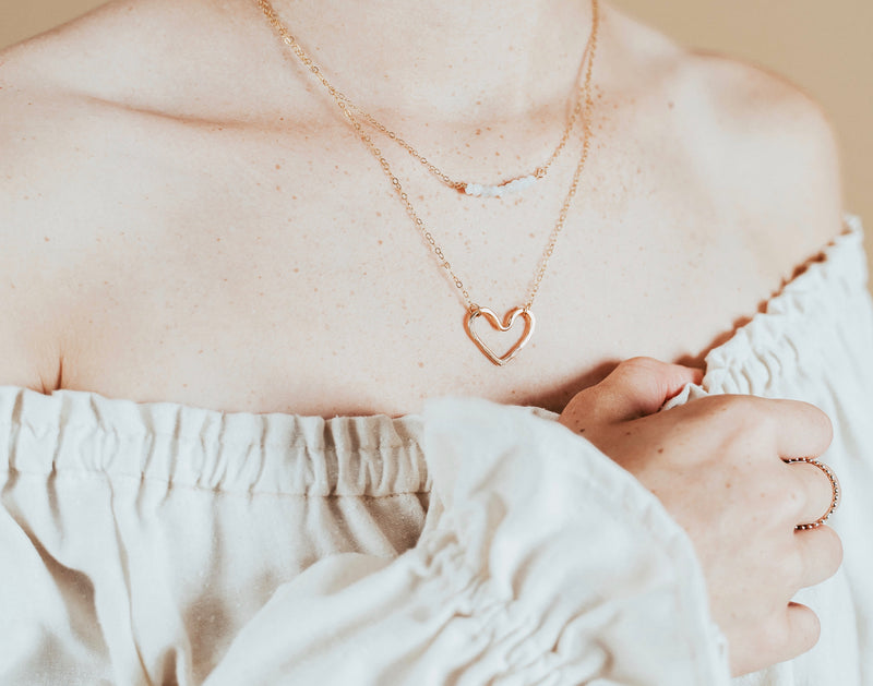 Our model wearing our small gold heart necklace