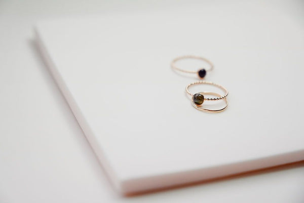 two gold solitaire rings and a simple stacker