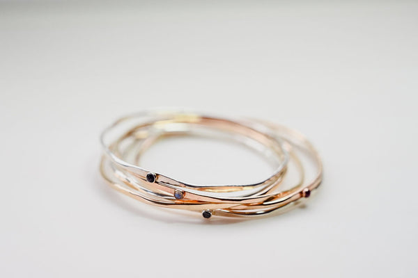 A stack of hex gold gemstone bangles