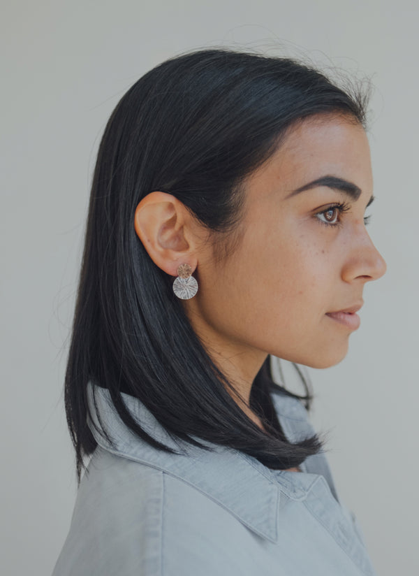 Our model wearing the asymmetrical disc studs