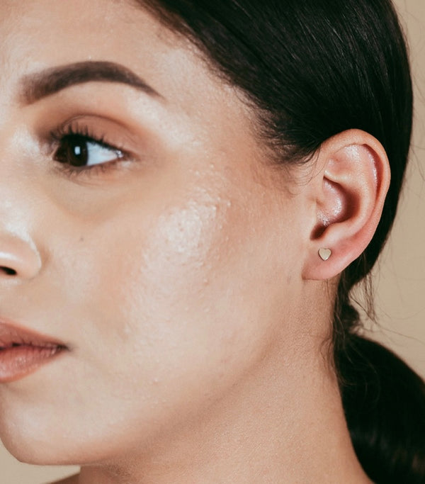 a closeup shot of our model wearing the gold heart studs