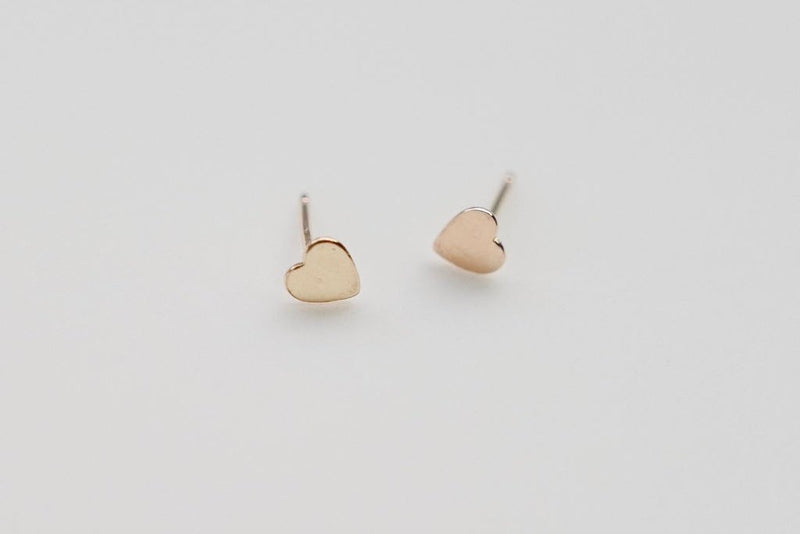 a small gold heart stud earring
