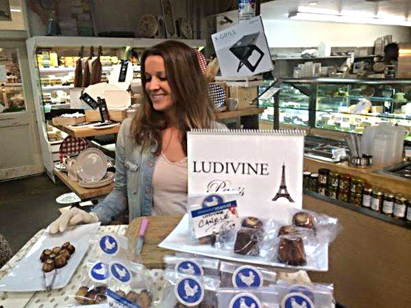 photo of Ludivine displaying Canelés and other baked specialties at Mr Marcel store in Los Angeles