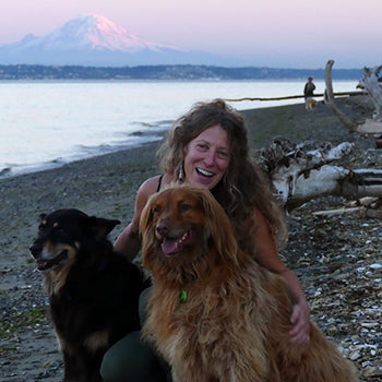 Neva Welton on the beach with her dogs with Mount Rainier in the background