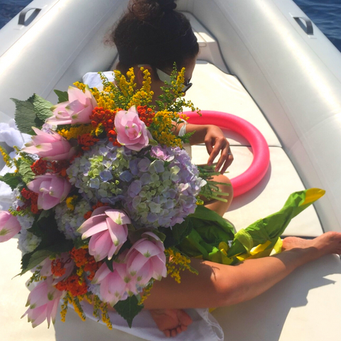 taking large bouquet of local Positano Italy flowers for a boat ride