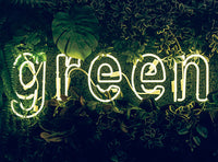 The word Green in fluorescent lights amongst green foliage