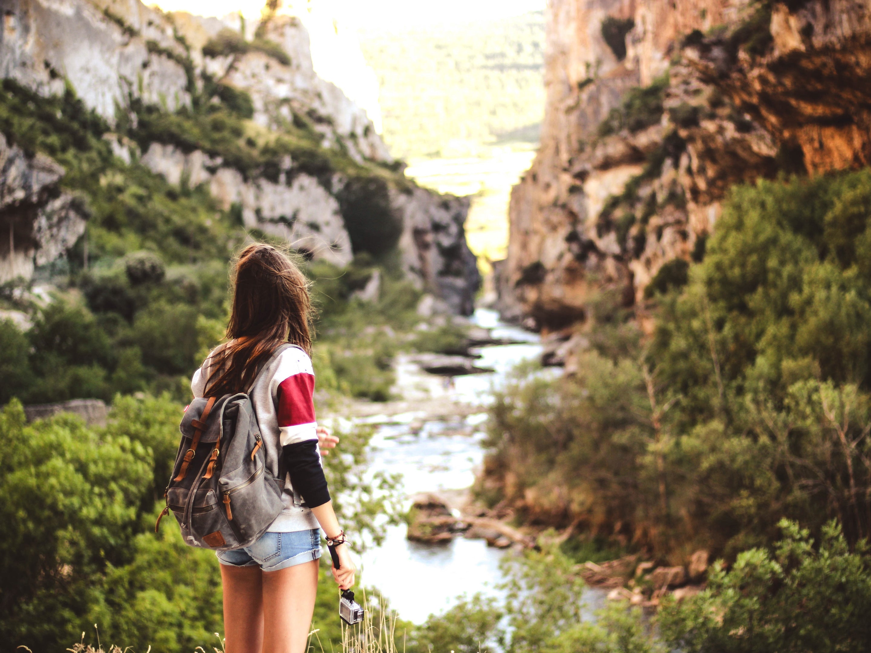 Brewed to save the planet - Woman with backpack hiking by a stream among mountains