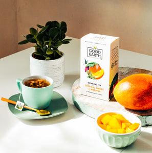 Good Earth Tropical Mango & Moringa Tea Breakfast Scene with Tea Bag in Cup and Package on table