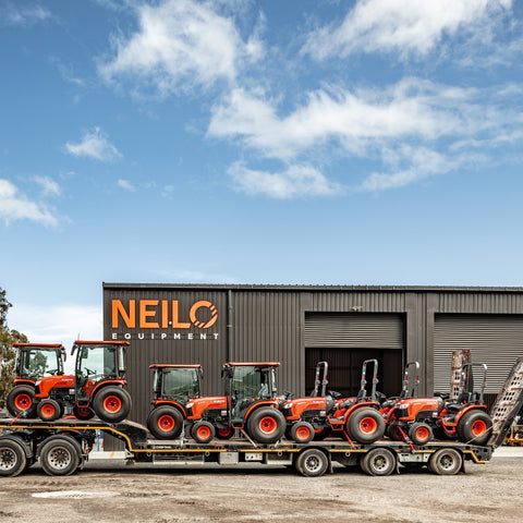 8 red kubota tractors on a larger trailer