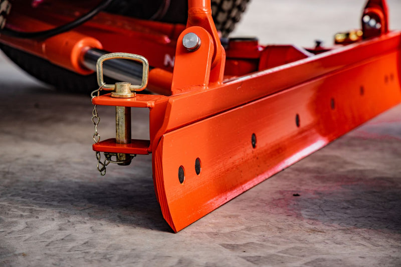 Close up angled view of orange grader blade