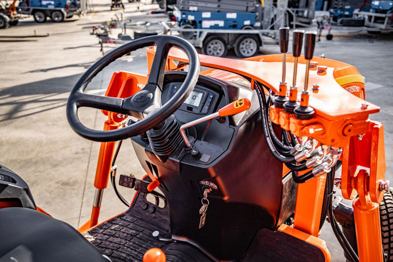 Inside tractor view of black steering wheel with orange interior