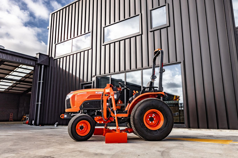 Side view of small orange tractor grader