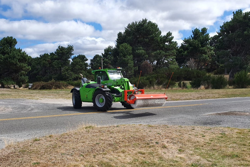 Neilo Telehandler attachment sweeping a gravel driveway