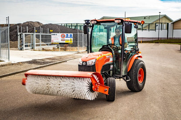Orange Kubota B3150 Tractor with large Neilo Broom on street