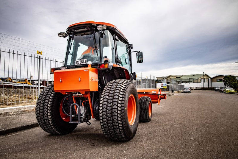 Rear view of Orange Kubota Tractor sweeper, sweeping driving along the road