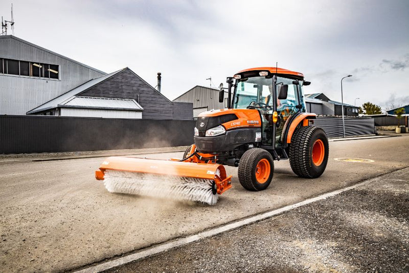 Side view of Orange Kubota Tractor sweeping a Street