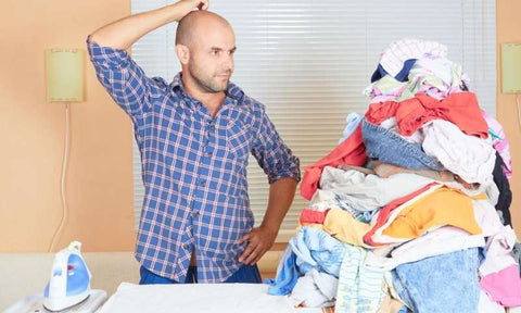 How to iron a shirt, man standing looking at pile of clothes