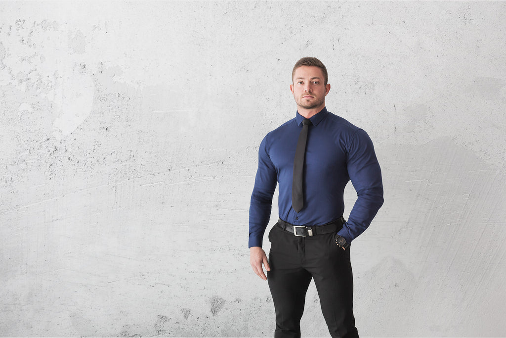 How to iron a shirt, man standing with muscle fit navy dress shirt with tie