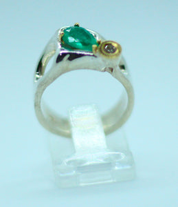A 1.5-carat emerald set in 950 silver with .10 natural diamond with an 18 k gold bezel.  This unique one of a kind design can go from day to night in a green flash.