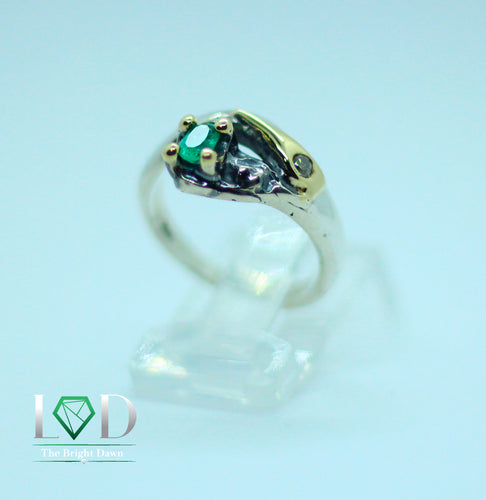 A 950 dainty silver band which is gracefully set with an oval cut emerald and a diamond on one side and then finished with 18 karat gold details.