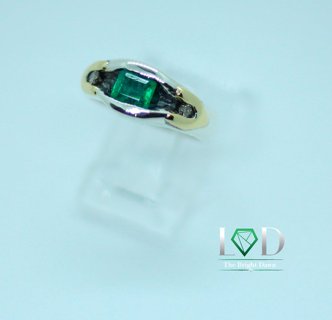 A perfectly green Colombian emerald of .30 carats pops with 2 diamonds, 18 karat gold and patinated silver decorations.