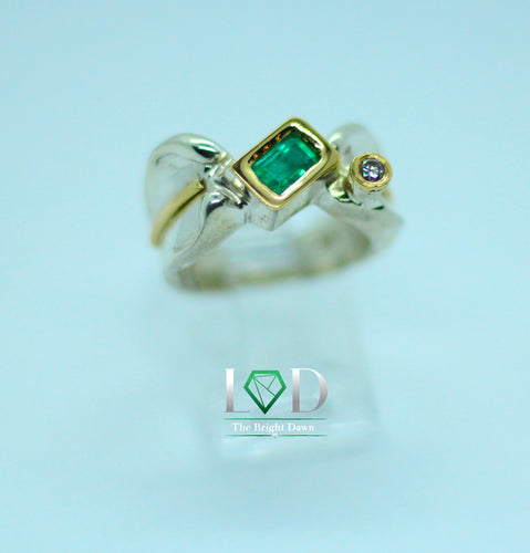 A very unique and modern design, this rectangular cut Colombian emerald of .80 carats is set in 950 silver with 1 diamond and 18 karat gold decorations.