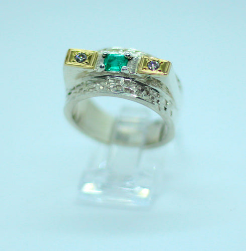 A .40 carat emerald cut Colombian emerald set with two diamonds, 18 karat gold and a textured band.  A modern but classic design fit for a king.