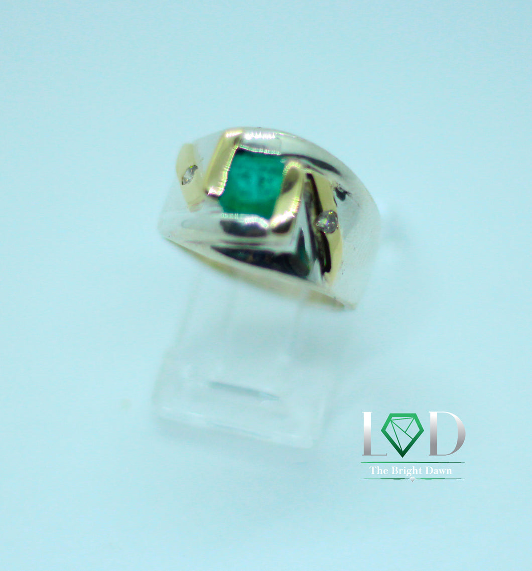 A 1.5 carat vibrantly green emerald set in a 950 silver band with 18 karat gold accents.  This ring will have people turning heads wherever you go.