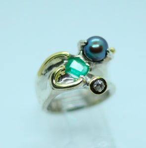 A rectangular cut .20 carat Colombian is the main focus in this 950 silver ring with 18 karat gold decorations.  It is accented by a brilliant coloured Tahitian pearl and a diamond.