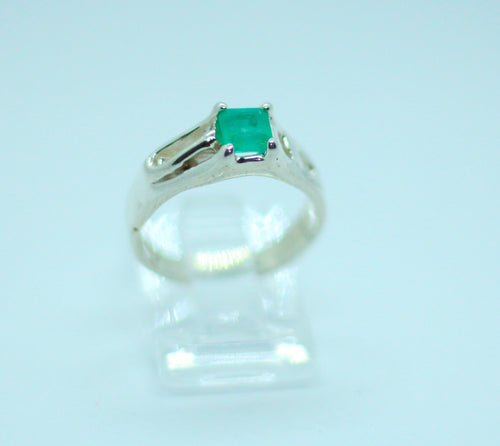 Princess cut .40 carat Colombian emerald set in 950 silver band approx. 4 cm thick.  The nails holding the stone have been decorated with 18 karat gold, which makes the vibrant bluish-green emerald pop. This dainty little ring will make your hands sparkle.