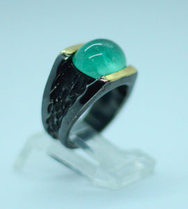 A 5.5-carat cabochon cut Colombian emerald set in patinated 950 silver with 18-karat gold decorations.