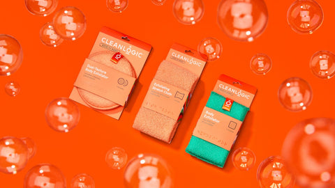 Flat lay image with three body scubbers that have Braille on the packaging on an orange background with bubbles floating above the scrubbers.