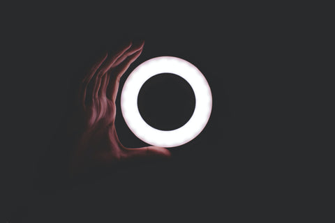 a hand holds a circular light in the darkness
