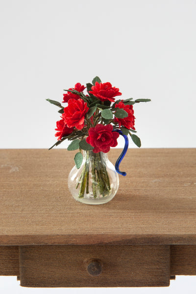 12th Scale Artisan Red Roses in a clear glass jug with a blue handle