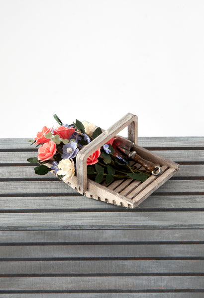 12th Scale Hand Made Wooden Flower Basket filled with summer flowers in apricots, cream and blue and a garden trowel