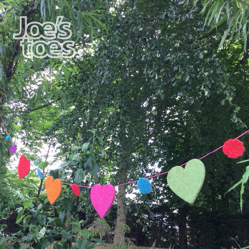 Joe's Toes felt garland showing completed bunting using 1.5m cord, felt flowers and large felt hearts with two pompoms