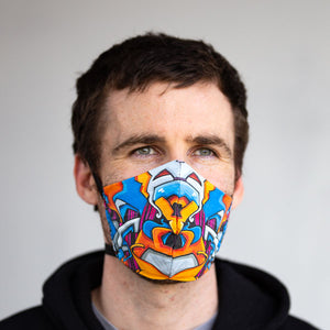 Graffiti art print fabric mask, on face, front view.